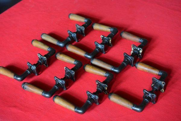7 gietijzeren setjes deurklinken met houten greep.